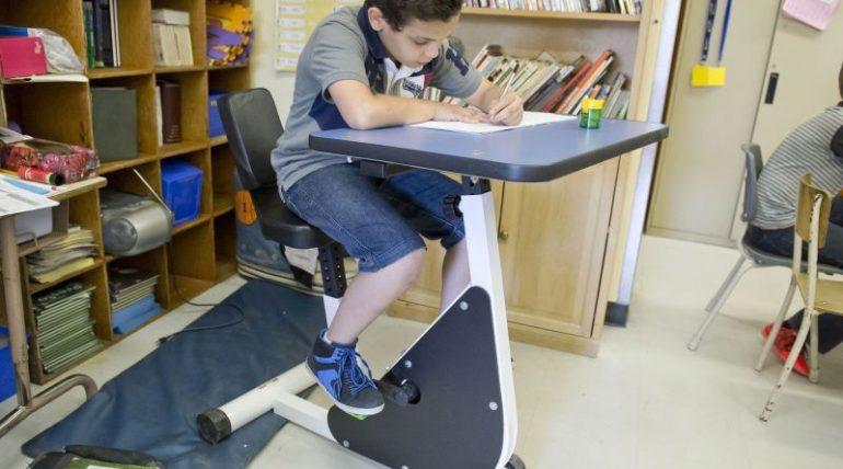 Criança sentada em mesa com pedais de bicicleta embaixo, pedalando enquanto estuda