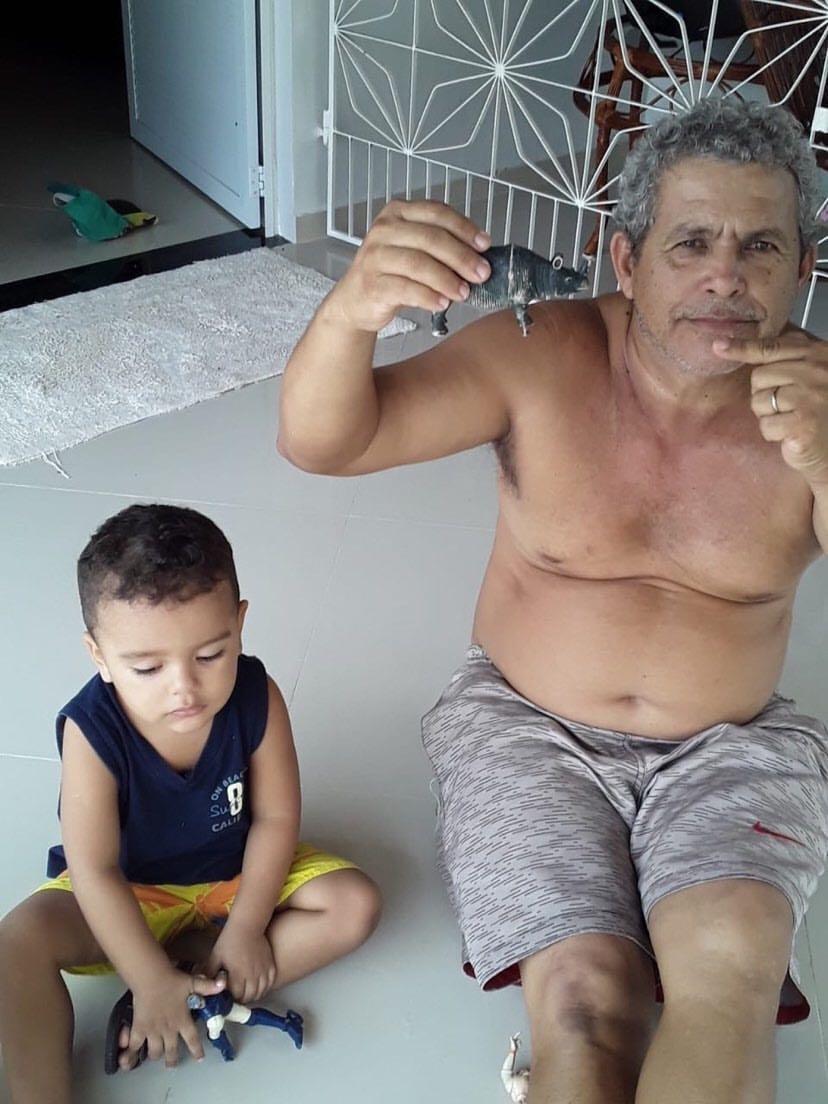 vovô que coloca próteses nos bonecos dos netos ao lado do neto e segurando um boneco