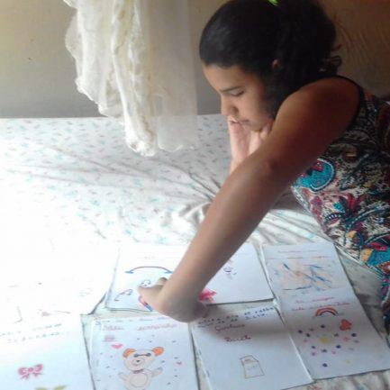 Após vaquinha, menina que vendia livros feitos à mão mostrando seus trabalhos