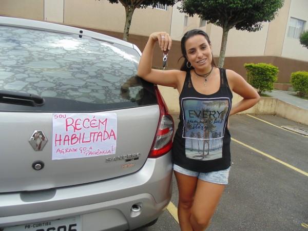 """mulher em frente ao carro que colou aviso com escrito """"recém-habilitada agradeço a paciência"""""""