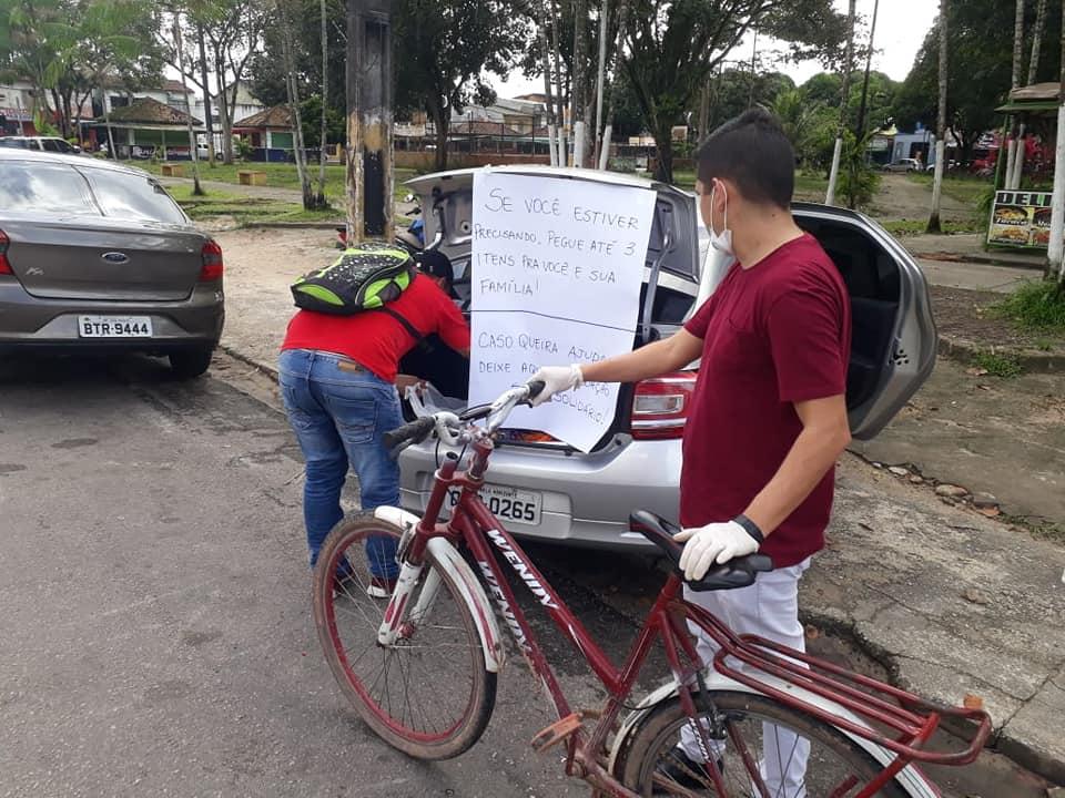 rapaz oferece alimentos para pessoas carentes porta-malas carro