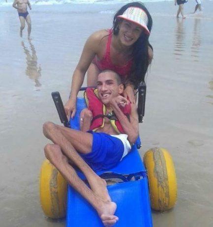 Irmã conduzindo irmão com paralisia cerebral em cadeira adaptada para tomar banho de mar