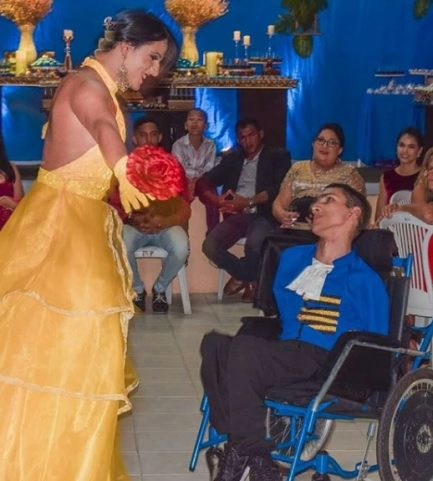 Irmã vestida de fera dançando valsa com irmão vestido de fera em cadeira de rodas no seu aniversário