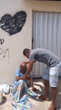 Homem carregando senho que foi abandonado pela família em rua que não conseguia andar