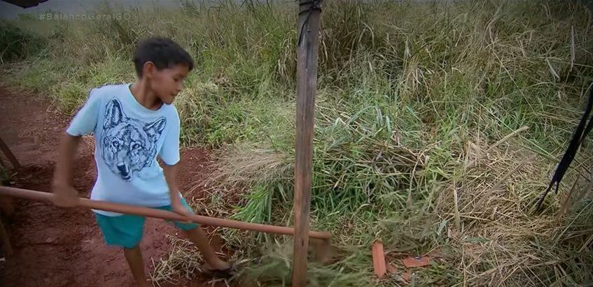 menino de 10 anos que trabalha sozinho capinando terreno