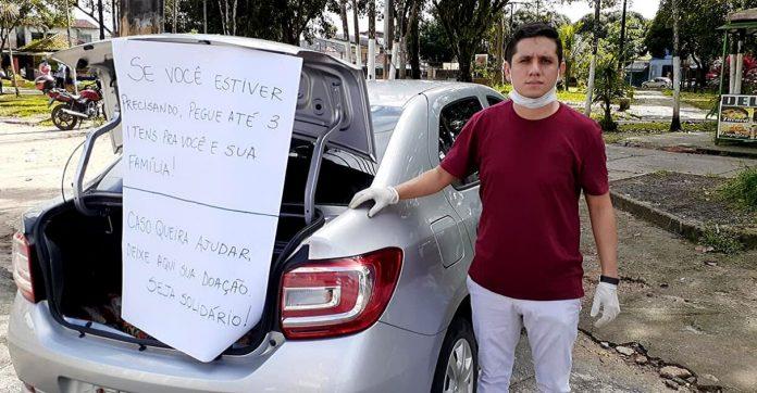 Com porta-malas aberto, rapaz oferece alimentos para pessoas carentes no PA 1
