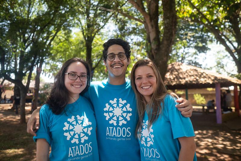 voluntários com camiseta do Adatados abraçados
