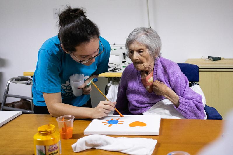 voluntária ajudando idosa com pintura em tela