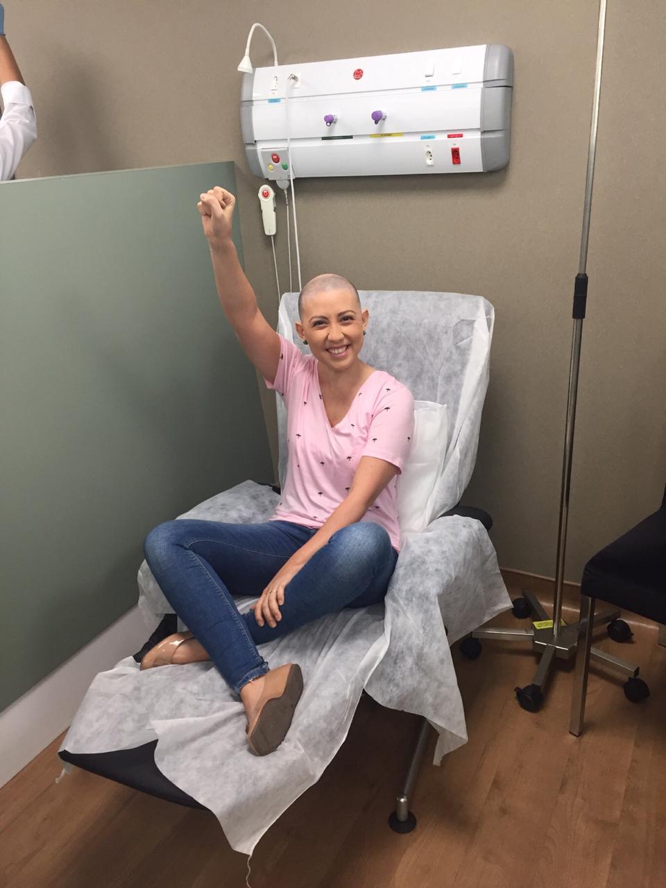 paciente câncer de mama poltrona hospital braço levantado sorrindo