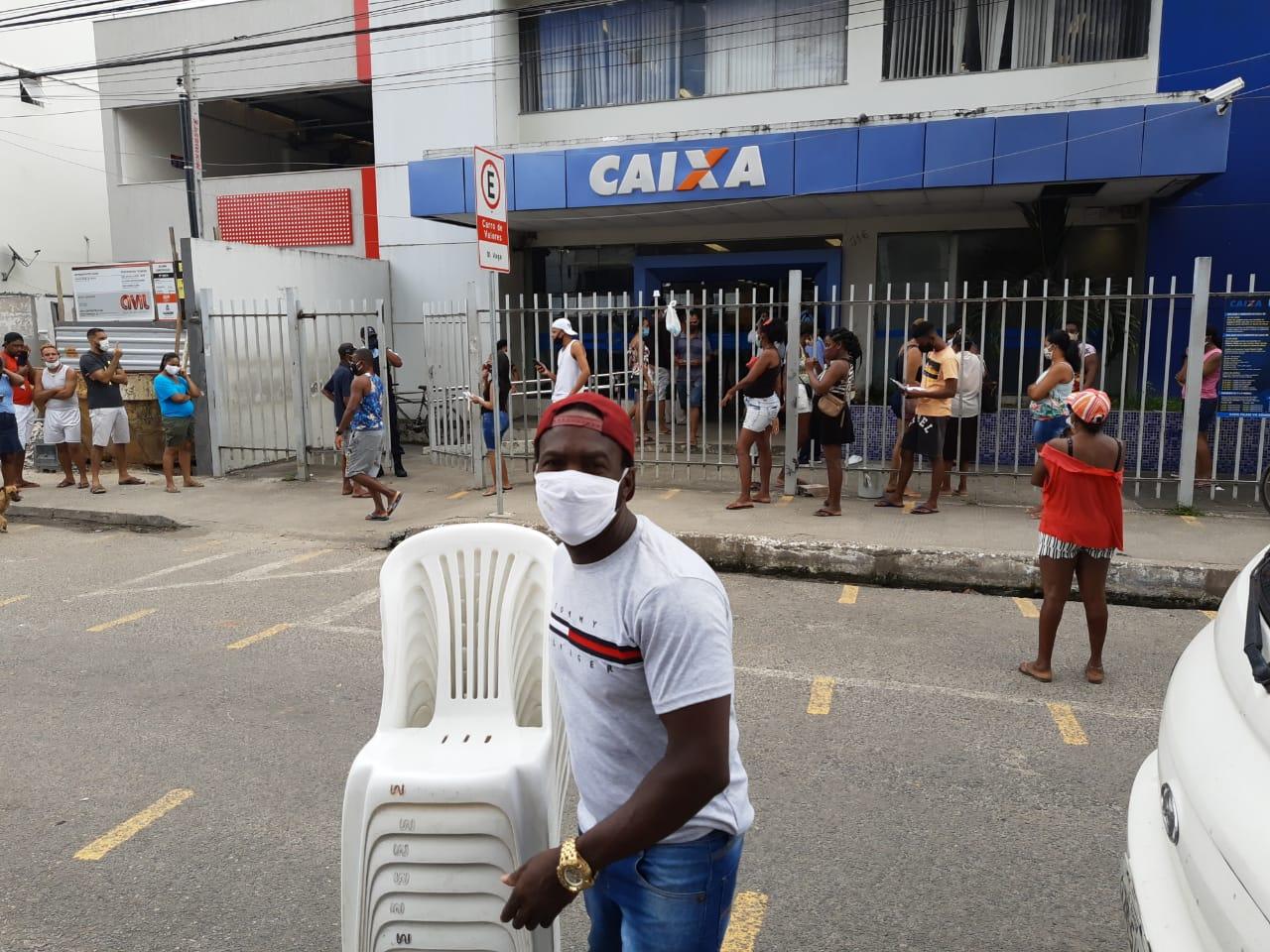 homem levando cadeiras pessoas fila caixa econômica federal