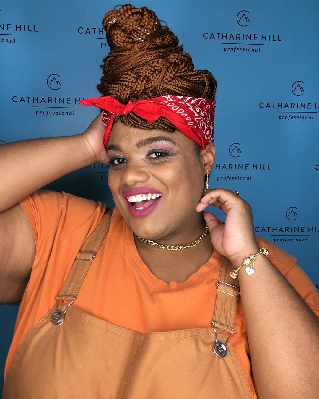 mulher trans preta gorda sorrindo mão cabelo