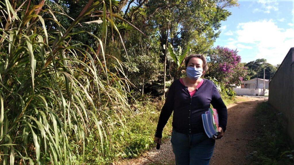 diretora escola segurando material didático rua terra