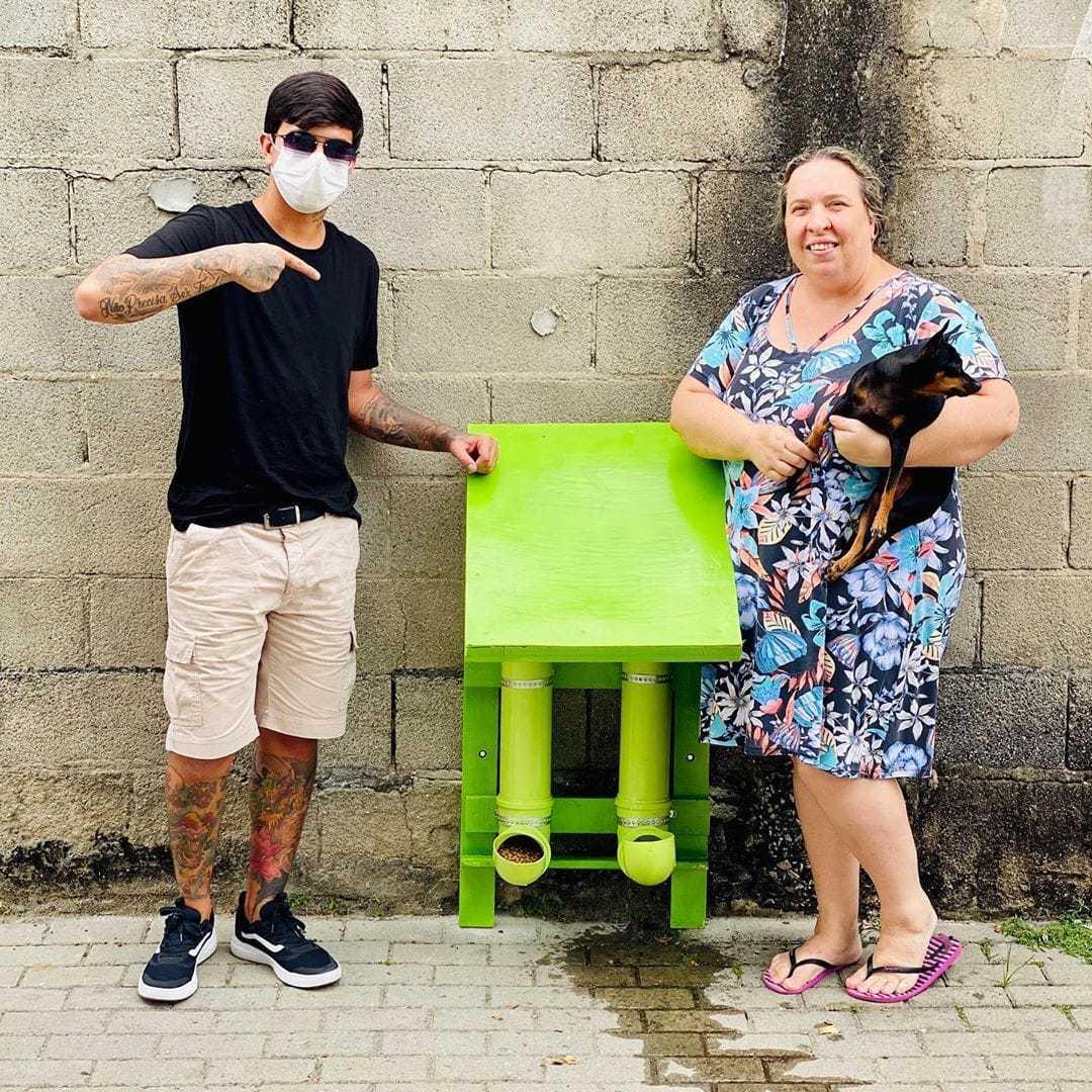 rapaz e mulher segurando cachorro ao lado comedouros bebedouros animais rua
