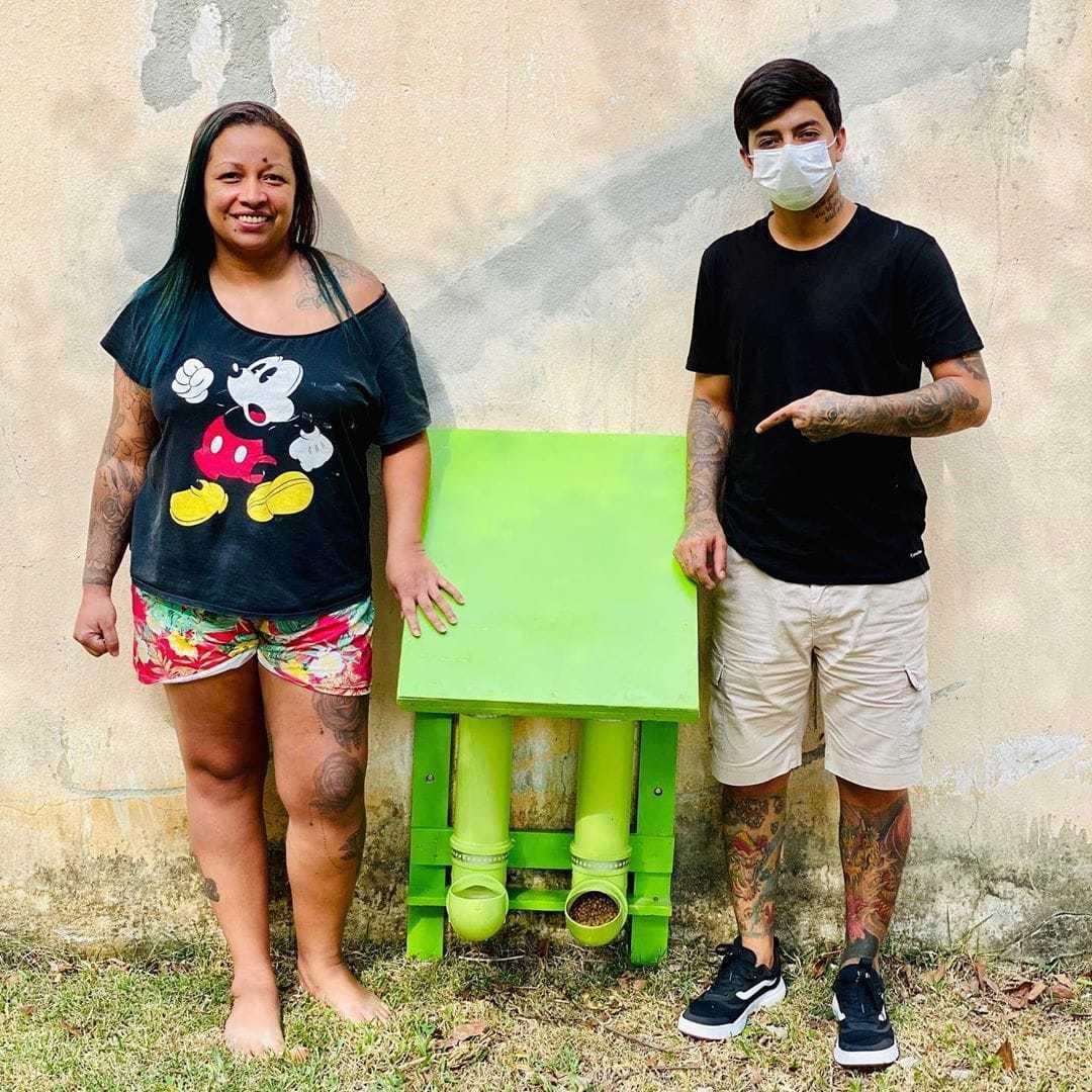 Mulher e rapaz ao lado comedouros bebedouros animais rua