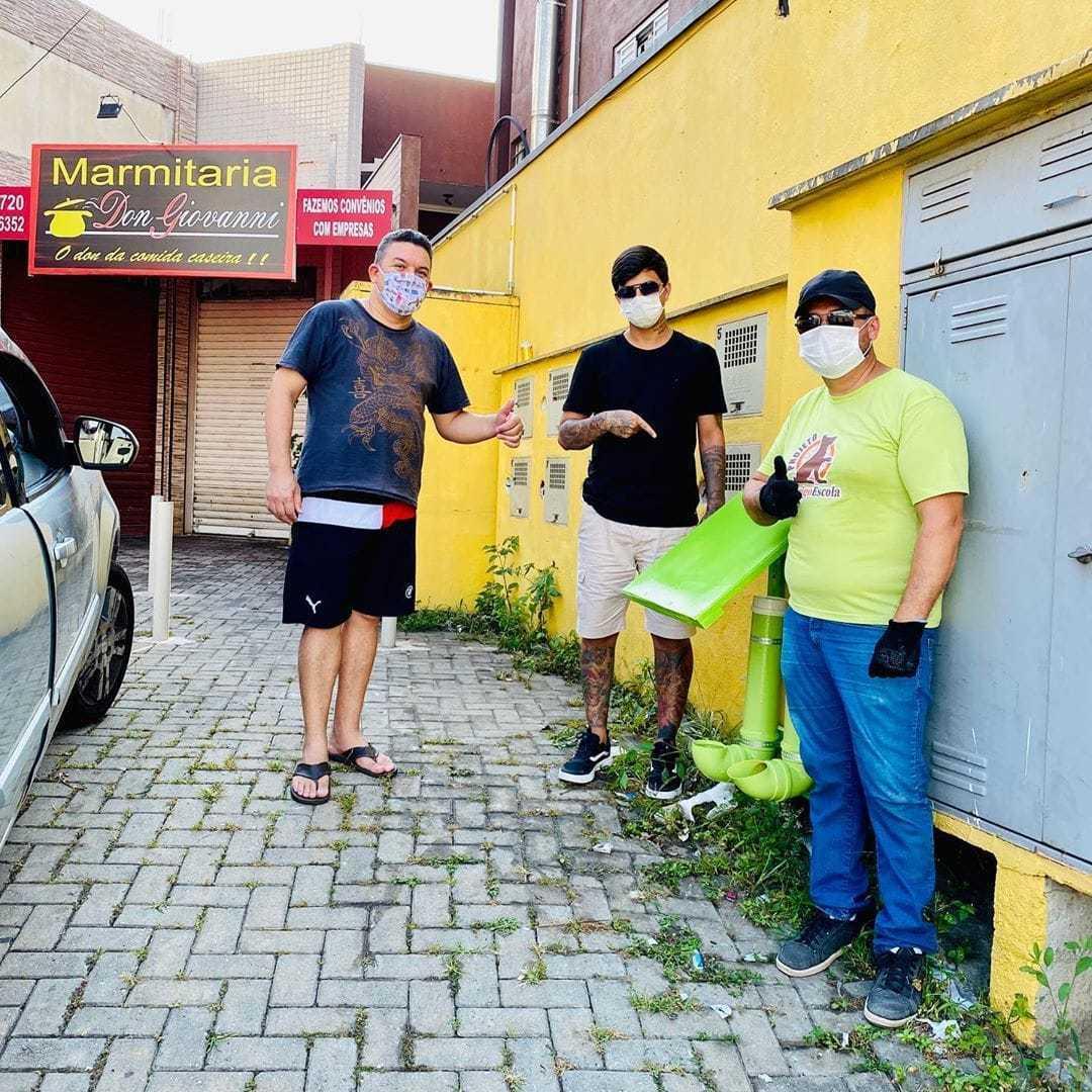 três rapaz ao lado comedouro bebedouro animais rua estacionamento loja