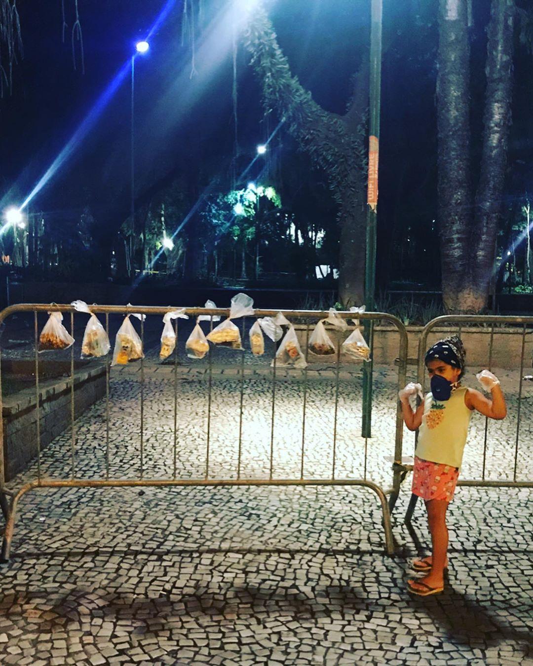 menina ao lado grade praça com lanches pendurados moradores de rua