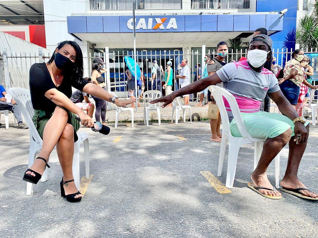 mulher e homem estendendo braços sentados cadeiras frente caixa econômica federal
