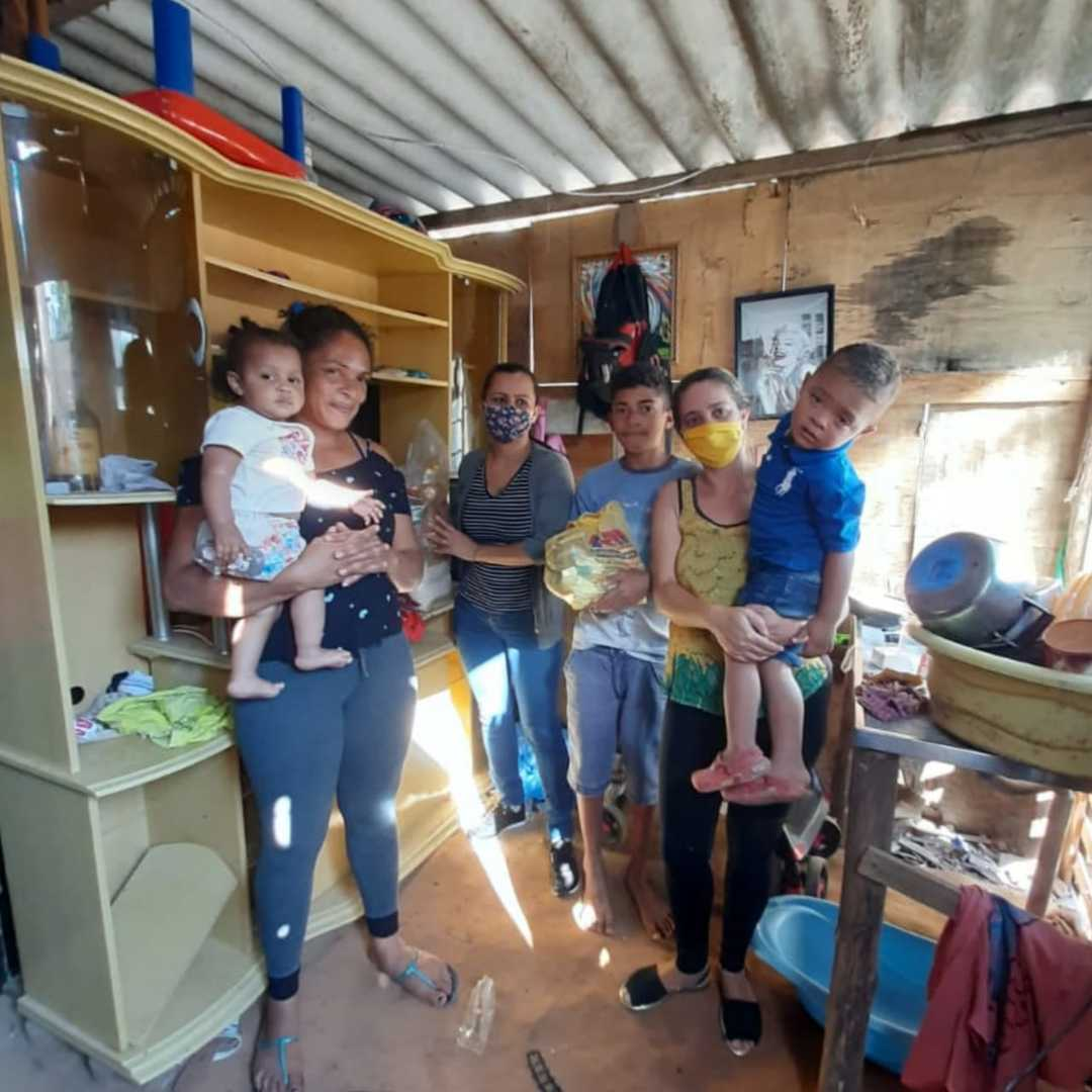 família barraco madeira segurando cesta básica