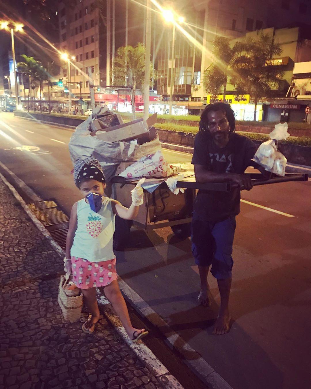 menina entregando lanche para morador de rua