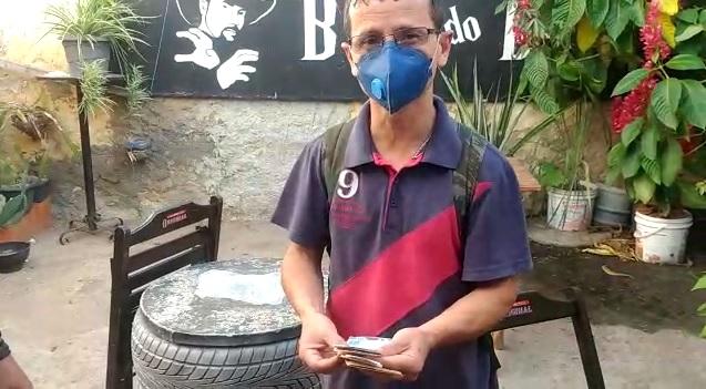 Vendedor de amendoim em pé usando máscara em quintal de casa