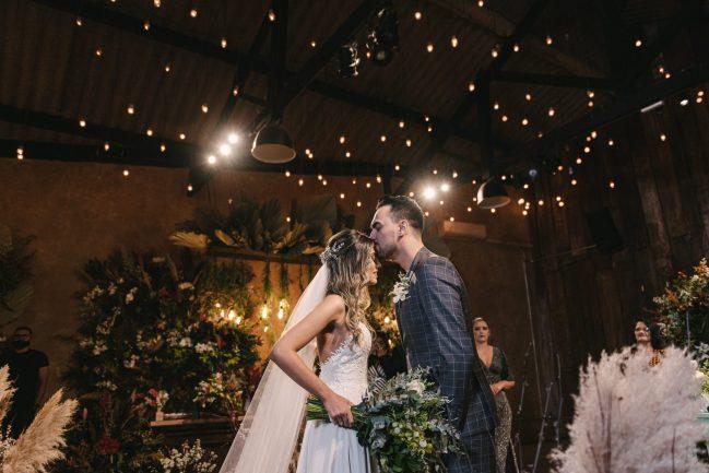 Imagem de noivo beijando a testa da noiva em casamento
