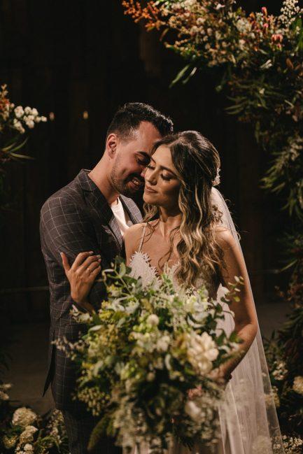 Noivo abraçando noiva com buquê em cerimônia de casamento