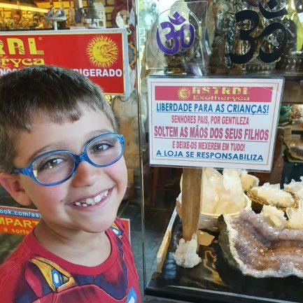 Criança sorrindo em loja com recado atrás