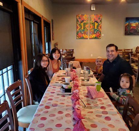 Imagem de garota com leucemia e sua família no restaurante