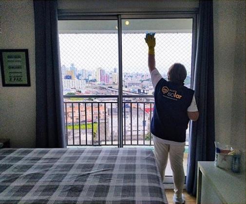 Mulher limpando janela de hospedagem de profissionais da saúde
