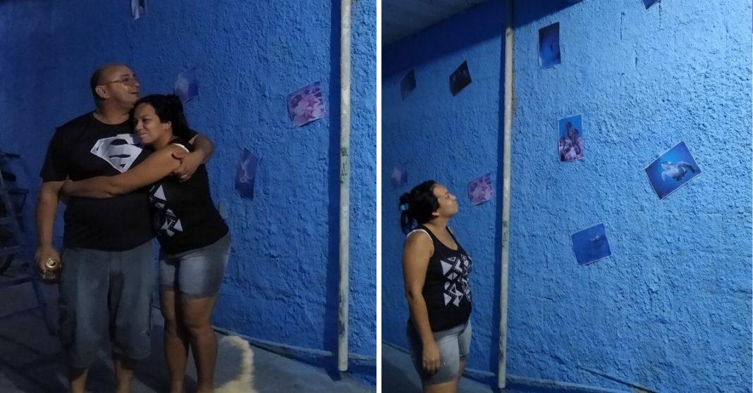 Esposa olhando para pintura de mar que marido fez na varanda para matar a saudade dela da praia