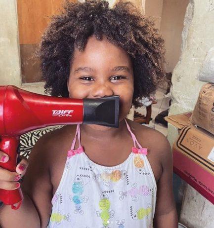 Menina posando para foto com secador de cabelo cobrindo o sorriso