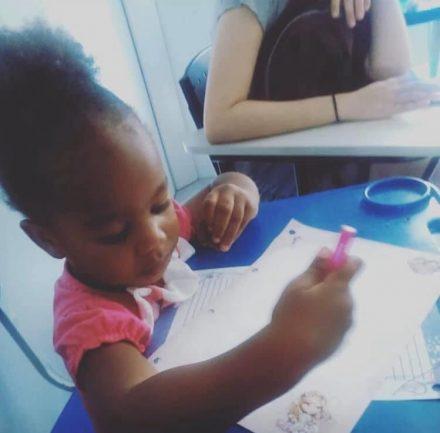 Menina sentada em carteira com lápis fazendo atividade