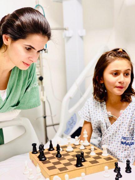 Imagem de médica jogando xadrez com criança em UTI