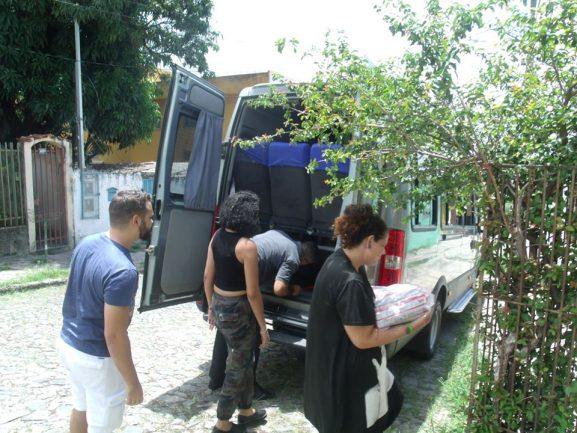 Imagem de funcionários de loja distribuindo alimentos para grupo de idosos do qual faz parte idosa que devolveu celular para a loja. Alimentos sendo retirados de van e colocados em mesa
