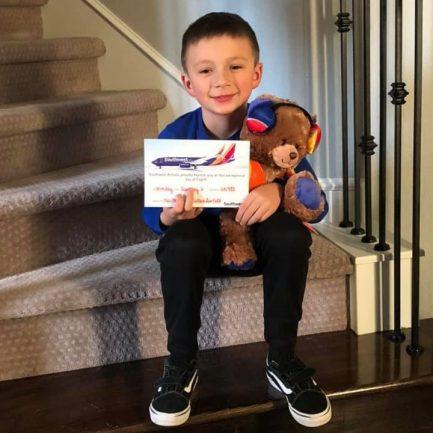 Criança com ursinho no colo na escada de casa e segurando cartão da companhia aérea