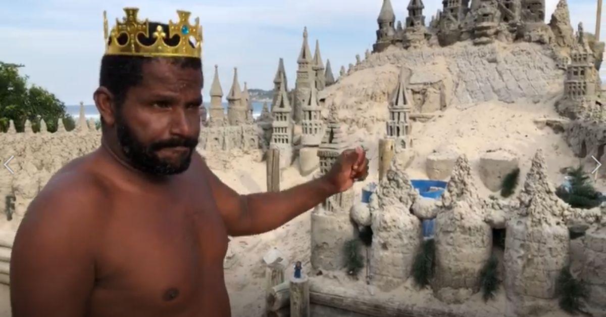 homem mostra castelo de areia