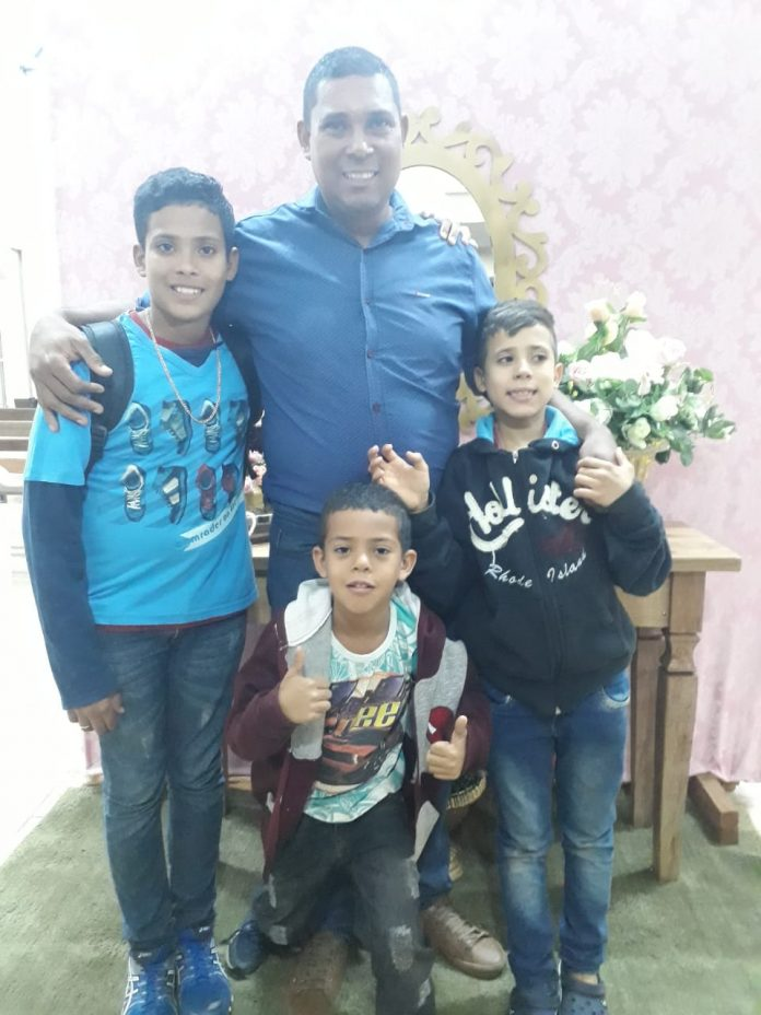 pai abraçado três filhos