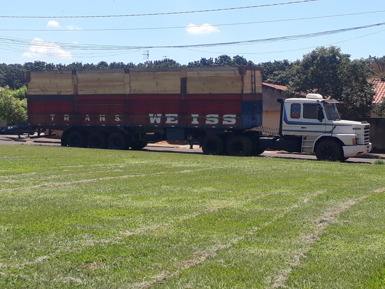 caminhão com carreta rua lado gramado