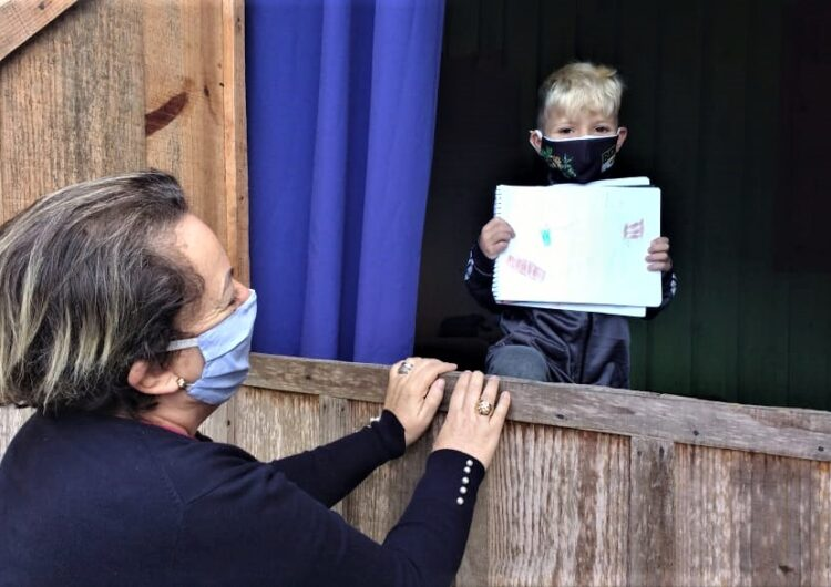 diretora escola entrega material aluno janela casa