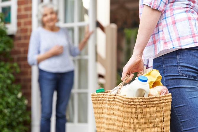 mulher carregando compras para idosa