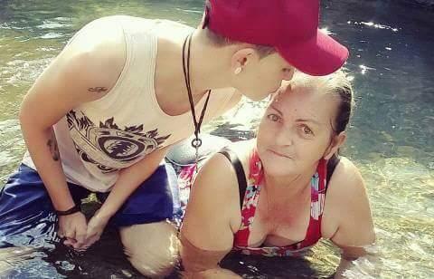 filho beijando testa mãe água cachoeira