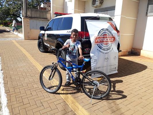 menino com bicicleta ao lado viatura policial