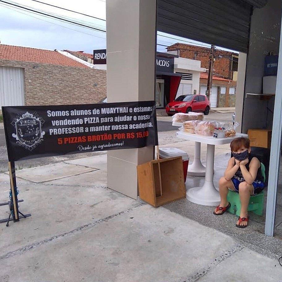menino sentado banquinho vendendo pizza academia