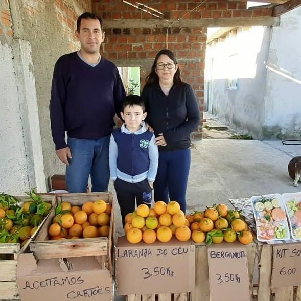 pai mãe filho vendendo tangerinas quintal casa
