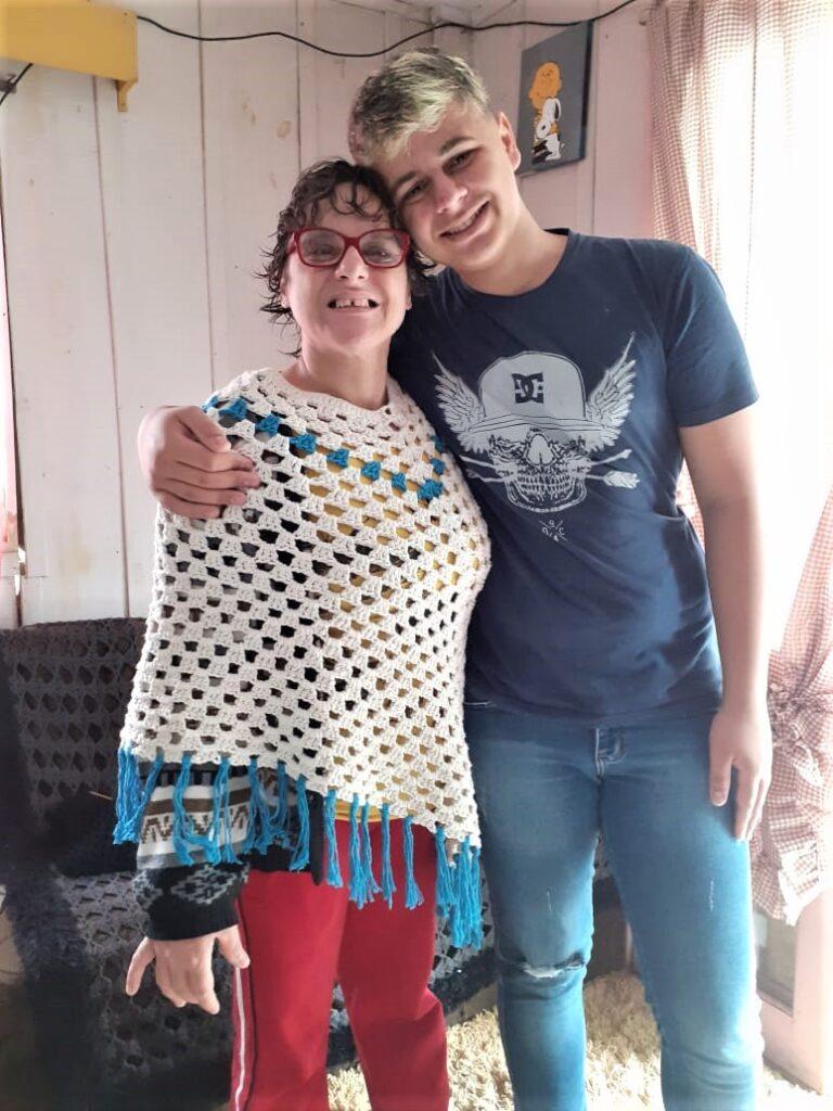 filho abraçando mãe vestida manta crochê