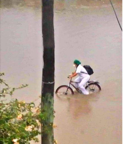Imagem de Auxiliar de Enfermagem de bicicleta em meio de uma enchente