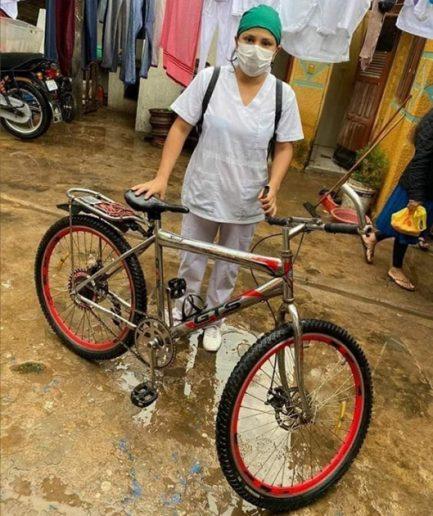 Imagem de Auxiliar de Enfermagem com bicicleta em quintal