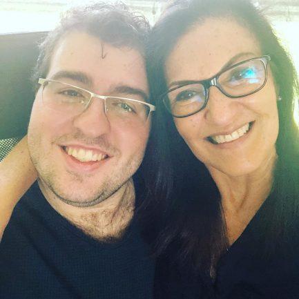 Mãe sorrindo ao lado de filho adulto com autismo