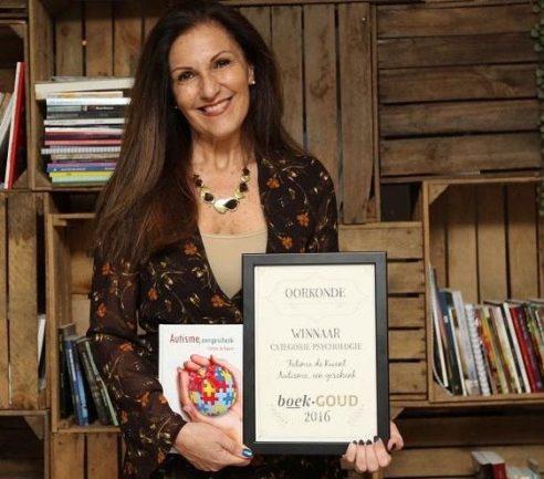 Mulher em frente a estante segurando livro sobre o autismo
