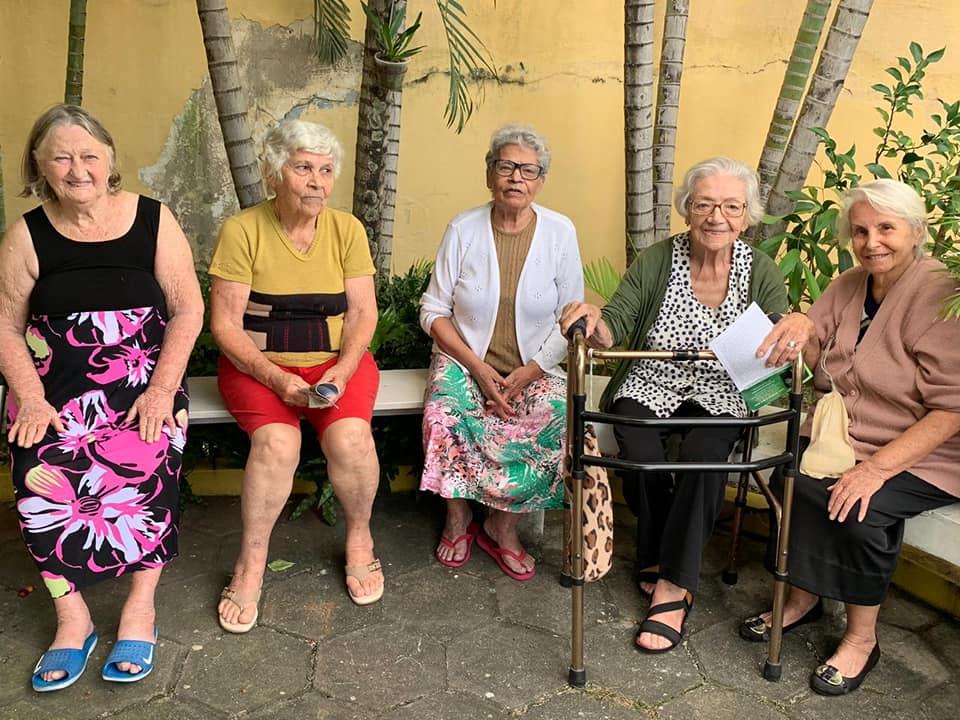cinco idosas sentadas banco asilo